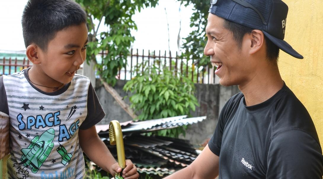 A Projects Abroad male intern is pictured having fun with a local child whilst on his physiotherapy internship in the Phillippines.